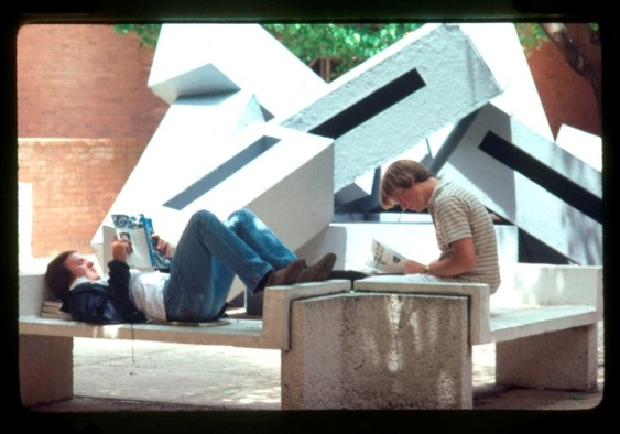 """Boxes,"" by Shane Eversfield Smith (1981). This installation was made by UMBC alumnus Shane Smith, circa 1981. It's possible that this sculpture was located near the Library for a student exhibition; the benches in the photograph suggest that it may have also been installed by the UC or Academic IV buildings. In an article from The Retriever (vol. 15, no. 2), Smith describes his work: ""Located in the upstairs library walkway, the ten identical modular units provide a glimpse of what may be the future in sculpture and design. As Smith put it, ""My art is a revealing science, in that it follows a specific experimental design. It is a perpetual quest forever present knowledge."" Smith continued to work on his sculpture and taught Dance classes at UMBC after he graduated."