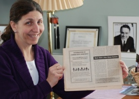 Michele Wolff, Director of the Shriver Center, displays a newspaper clipping from February 2000 that advertises the Shriver Living Learning Center (SLLC), UMBC's first living learning community. The SLLC was launched for the Fall 2000 semester with 16 student residents. A portrait of R. Sargent Shriver can be seen at right.