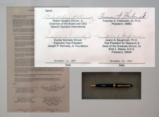 Michele Wolff has several items framed and hanging in her office, including the memorandum of understanding that created the Shriver Center on December 14, 1993. The MOU is signed by R. Sargent Shriver, Eunice Shriver, and Freeman Hrabowski. The pen used to sign the MOU is also framed.