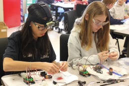 Engineers at Old Mill STEM Middle School connect the sensors on their robots.